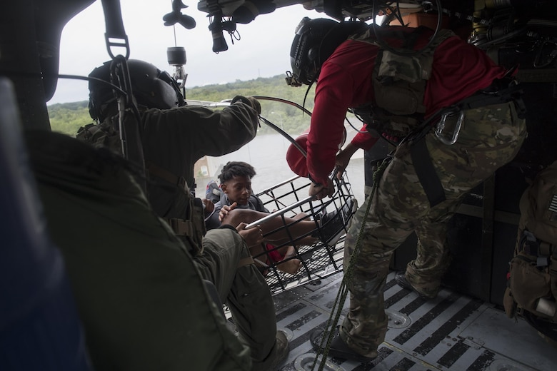 A special missions aviator from the 41st Rescue Squadron, and a pararescueman from the 38th Rescue Squadron, secures a basket carrying evacuees, Aug. 30, 2017, over a residence in the Houston, Texas area.