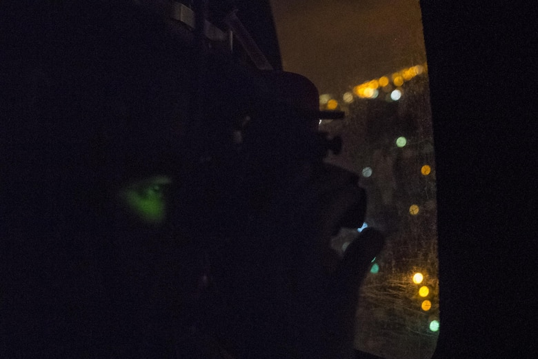 A Pararescueman from the 38th Rescue Squadron scans the ground with night vision for those that might need evacuated, Aug. 30, 2017, in the Houston, Texas area.
