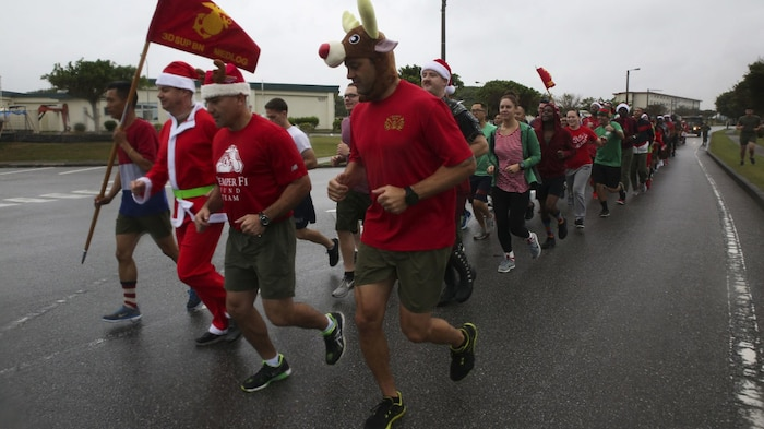 Marines and Sailors with Medical Logistics Company, 3rd Supply Battalion, Combat Logistics Regiment 35, run across base during the 7th Annual Jingle Bell Run hosted by Marine Corps Community Services at Camp Kinser, Okinawa, Japan Dec. 1, 2017.