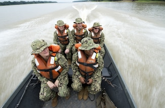 A team of five U.S. Navy doctors travel in a boat to a remote village along the Amazon River in Brazil.