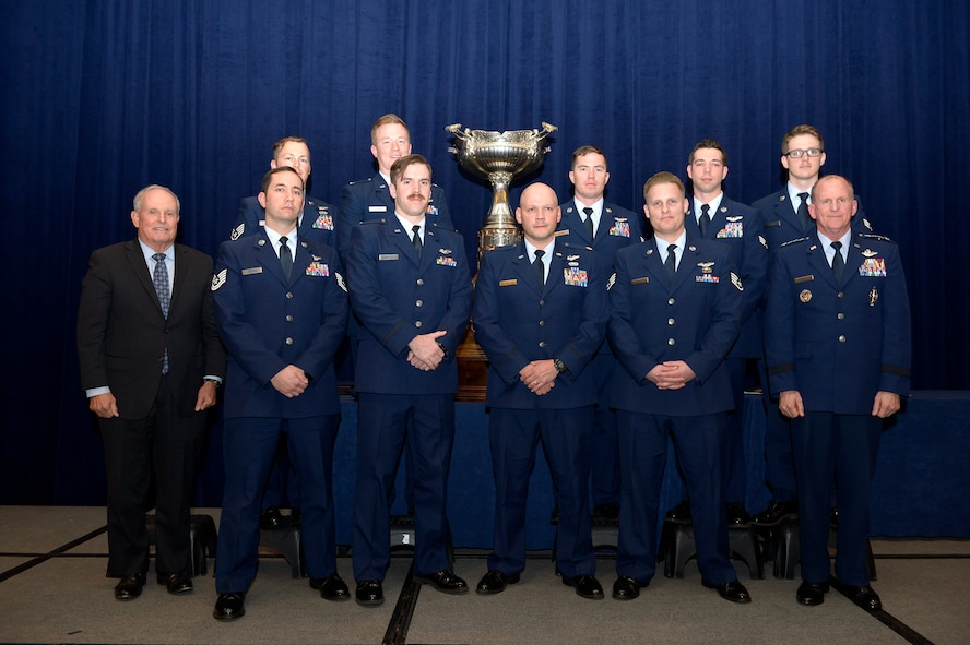 "Members of the AC-130U Gunship aircrew known as ""Spooky 43"" Air Force Vice Chief of Staff Gen. Stephen W. Wilson and Lt. Gen. (Ret.) Stephen Wood pose for a photo in front of the MacKay trophy Nov. 29, 2017, in Arlington, Va.  The aircrew received the trophy during an awards dinner. First awarded in 1912, the Mackay Trophy honors the most meritorious U.S. Air Force flight of the previous year. (U.S. Air Force photo by Staff Sgt. Rusty Frank)"