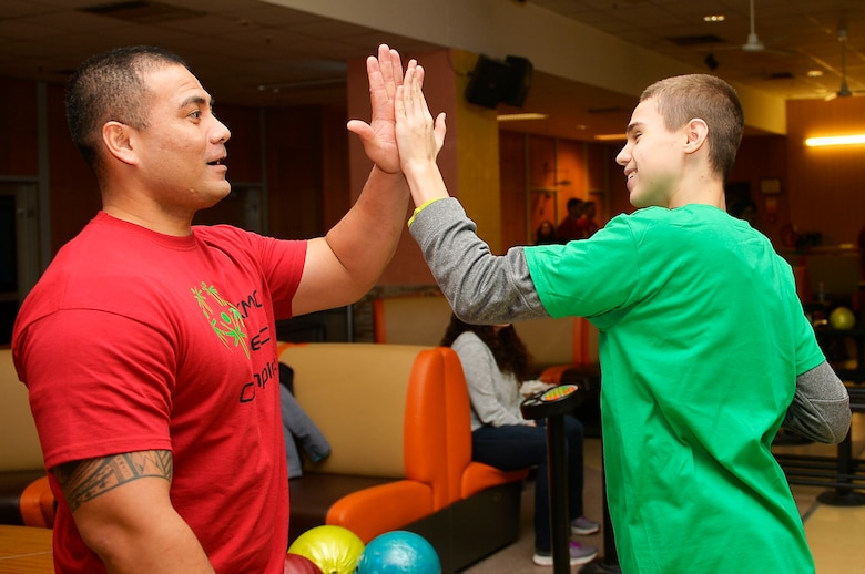 U.S. Army Sgt. 1st Class Rahim Fuiava, 773rd Civil Support Team information system analyst, congratulates a participant during the Kaiserslautern Military Community Winter Special Olympics on Vogelweh Special Military Complex, Germany, Dec. 1, 2017. The KMC Special Olympics occurs every spring and winter, and involves students from both German and American schools. (U.S. Air Force photo by Airman 1st Class Joshua Magbanua)