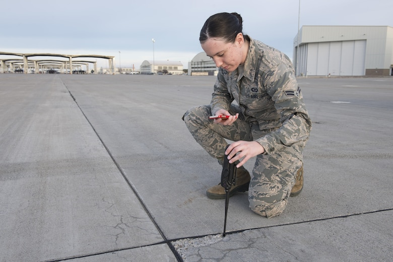 Airman 1st Class Sabrina Watson, 366th Operations Support Squadron airfield management coordinator takes a photograph of a crack in the runway Nov. 30, 2017, at Mountain Home Air Force Base, Idaho. Once completing checks for cracks or debris on the runway the information is tracked in a log and submitted to the 366th Civil Engineer Squadron to be fixed. (U.S. Air Force photo by Senior Airman Lauren-Taylor Levin)