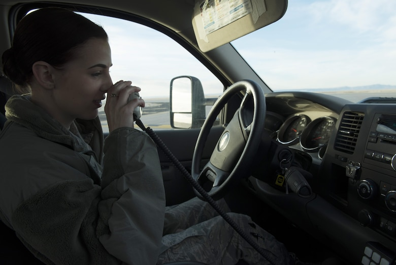 Staff Sgt. Gabrielle Swift, 366th Operations Support Squadron airfield management operations supervisor, calls the air traffic control tower for clearance to cross the runway Nov. 30, 2017, at Mountain Home Air Force Base, Idaho. Swift and others from the airfield management team do daily checks for wildlife on the runway, cracks in the pavement and debris that could cause damage to aircraft. (U.S. Air Force photo by Senior Airman Lauren-Taylor Levin)