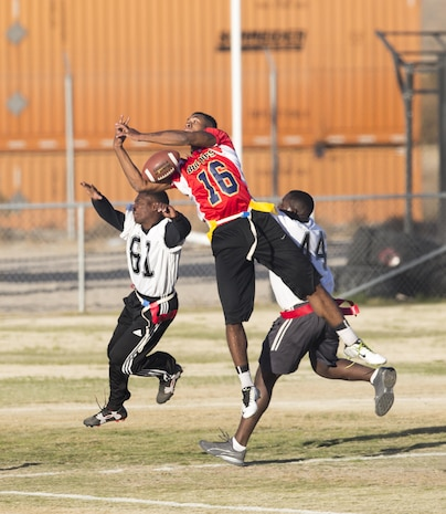 Lance Cpl. Jacob Brown (16), between two defenders, lets a potential touchdown slip through his arms, during the first Turkey Bowl held aboard Marine Corps Logistics Base Barstow Nov. 21. The Marine Reservists assigned to Fleet Support Division took the championship trophy.