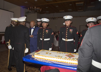 Lieutenant General Ronald Bailey, USMC Retired, and Colonel Sekou Karega, commanding officer, Marine Corps Logistics Base Barstow, serve the traditional first piece of birthday cake to the eldest Marine present, Sgt. Maj. Lonnie Long, USMC Retired, during the 242nd Marine Corps Birthday Ball ceremonies held at Big Bear Lodge, Big Bear, Calif., Nov. 18.
