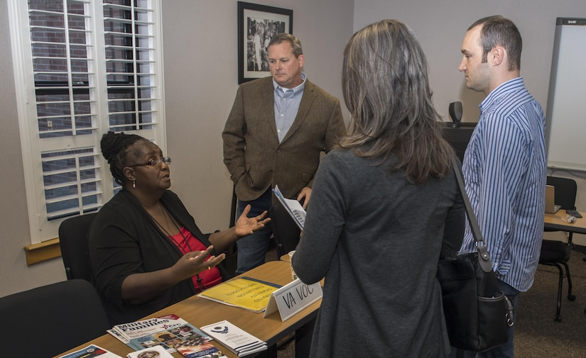 Tresia A. Frazer, left, vocational rehabilitation counselor, speaks with Staff Sgt. Robert Gibson, right, 628th Security Force Squadron and his wife Sadie Gibson as Bill Oldenburg, center, Education and Employment Initiative and Operational Warfighter regional coordinator – Mid-Atlantic, looks on during the Second Annual Warrior Care Breakfast and Information Fair at the Airman & Family Readiness Center here Nov. 29, 2017.
