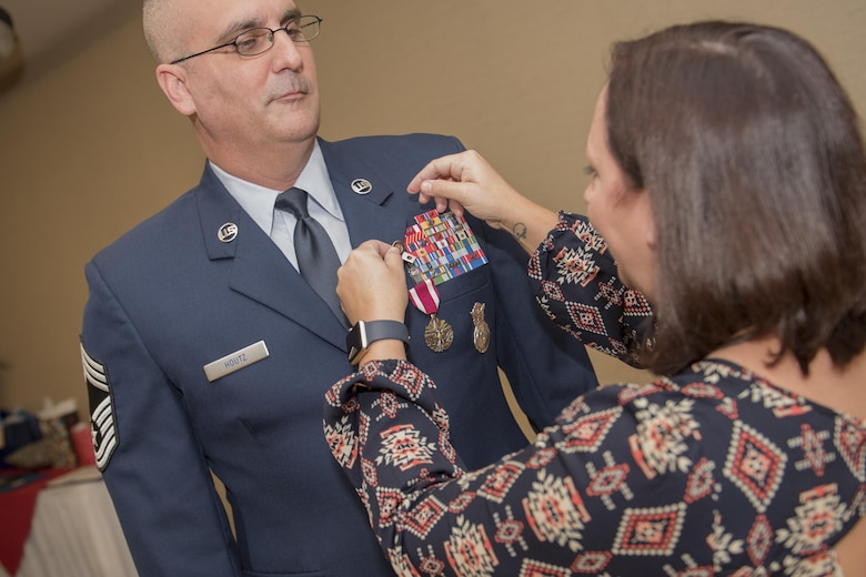 Beth Houtz places a retirement pin on her husband, Chief Master Sgt. David Houtz, 823d Base Defense Squadron chief enlisted manager's lapel, during his retirement ceremony, Dec. 1, 2017, at Moody Air Force Base, Ga. Houtz enlisted in the Air Force on Oct. 6, 1991. During his 27-year career, he has held numerous leadership roles while supporting Operations Provide Promise, Southern Watch, Enduring Freedom, Iraqi Freedom and Inherent Resolve. (U.S. Air Force photo by Senior Airman Daniel Snider)