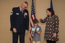 Chief Master Sgt. David Houtz, 823d Base Defense Squadron chief enlisted manager, and his wife, Beth, present their son, Logan, with an appreciation award, during Houtz's retirement ceremony, Dec. 1, 2017, at Moody Air Force Base, Ga. Houtz enlisted in the Air Force on Oct. 6, 1991. During his 27-year career, he has held numerous leadership roles while supporting Operations Provide Promise, Southern Watch, Enduring Freedom, Iraqi Freedom and Inherent Resolve. (U.S. Air Force photo by Senior Airman Daniel Snider)