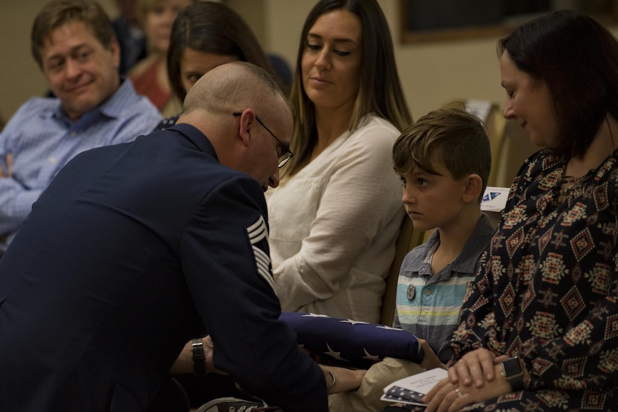 Chief Master Sgt. David Houtz, 823d Base Defense Squadron chief enlisted manager, presents his son, Logan, with a U.S. flag during Houtz's retirement ceremony, Dec. 1, 2017, at Moody Air Force Base, Ga. Houtz enlisted in the Air Force on Oct. 6, 1991. During his 27-year career, he has held numerous leadership roles while supporting Operations Provide Promise, Southern Watch, Enduring Freedom, Iraqi Freedom and Inherent Resolve. (U.S. Air Force photo by Senior Airman Daniel Snider)