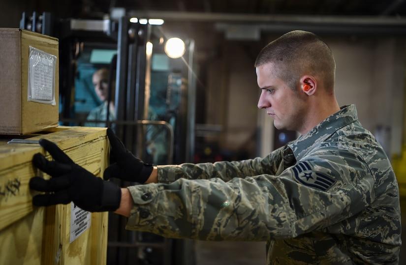 Staff Sgt. George Garner, 437th Aerial Port Squadron shift supervisor, steadies cargo during a pallet build at Joint Base Charleston, S.C., Nov. 29, 2017.