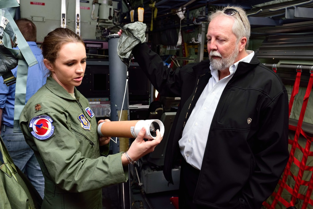 """Maj. Ashley Lundry, 53rd Weather Reconnaissance Squadron aerial reconnaissance weather officer and chief scientific officer, shows a weather data-gathering instrument called a dropsonde to Dr. Fred """"Marty"""" Ralph, Researcher and Director for the Center of Western Weather and Water Extremes, Scripps Institute of Oceanography, Nov. 29, 2017, at Brown Field Airport, San Diego, California. Hurricane Hunters met with Ralph and other Scripps scientists that day to discuss plans for participating in atmospheric river reconnaissance missions in early 2018. (U.S. Air Force photo by Tech. Sgt. Ryan Labadens)"""