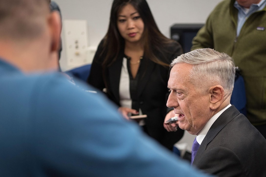 Defense Secretary James N. Mattis talks to reporters aboard an aircraft.