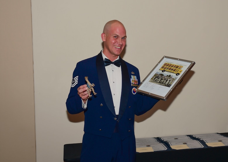Tech Sgt. Travis Jackson, 460th Force Support Squadron Airman Leadership School raptor flight instructor, receives a gift from the graduating class during their graduation Nov. 29, 2017, on Buckley Air Force Base, Colorado.