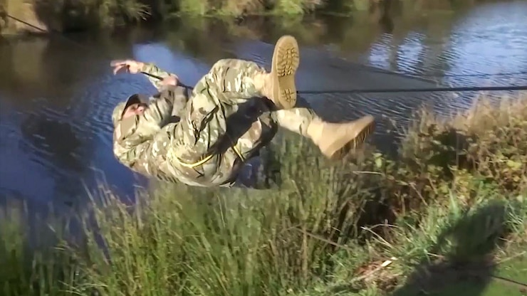 A soldier hanging from a rope bridge by his hands and legs maneuvers across a body of water.