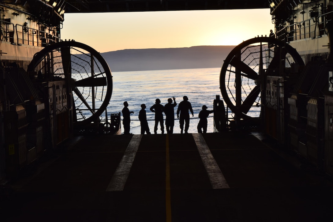 U.S. Navy landing craft, air cushion crew members with Assault Craft Unit 5 watch the sunrise off the western coast of San Clemente Island from the USS Anchorage well deck while preparing to conduct expeditionary advanced base operations during Exercise Dawn Blitz, Oct. 24, 2017. Dawn Blitz 17 provides an opportunity for collaboration between Navy and Marine Corps counterparts in the establishment of scalable and agile expeditionary advanced bases capable of expanding littoral maneuver capabilities.