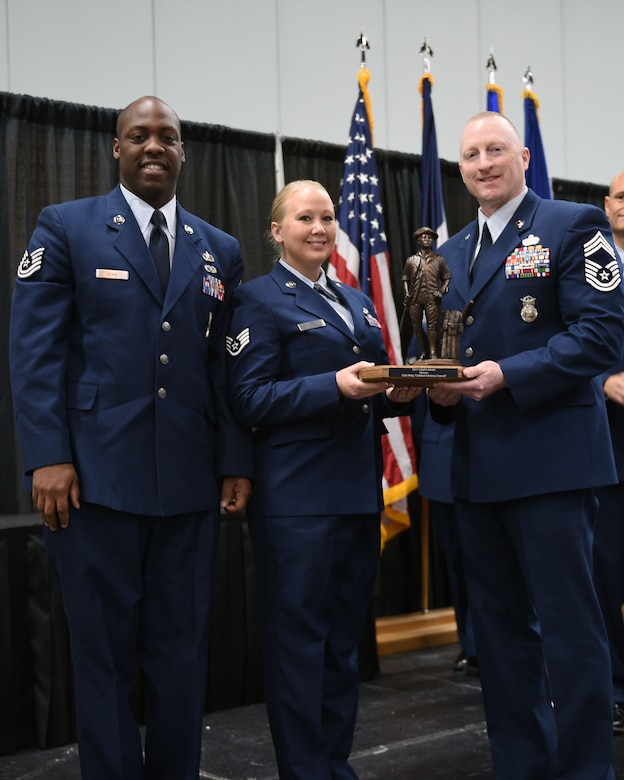 Chief Master Sgt. John Smith poses with Staff Sgt. Jaime Young and Tech. Sgt. Marcus Goins, who accepted the Chief's Award on behalf of the Enlisted Advisory Council (EAC) at the Annual Awards Ceremony at Hy-Vee Hall, Des Moines, Iowa on November 4, 2017. The EAC earned this award due to their continued work and dedication in raising the 132d Wing's Airmen and their families morale. (U.S. Air National Guard photo by Airman 1st Class Katelyn Sprott)