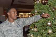 Tech. Sgt. Brandon Godfrey, Command Support Staff, 161st Air Refueling Wing, places an ornament on a Christmas tree in the wing's Dining Facility during the Unit Training Assembly here Dec. 3, 2017. Godfrey grew up playing basketball and seeks to use it as an instrument to teach children the value of integrity, hard work and dedication. (U.S. Air National Guard photo by 2nd Lt. Tinashe Machona)