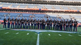 Marines with Recruiting Station Denver pose on the Denver Broncos field before the Military Appreciation Game at the Sports Authority Stadium in Denver, CO, November 12, 2017.