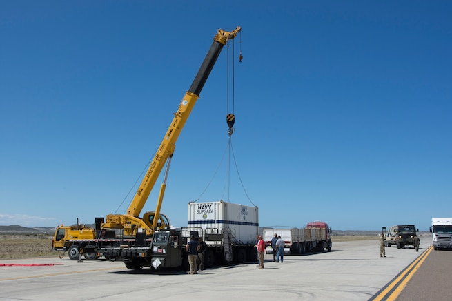 A cargo container is hoisted onto a truck bed.