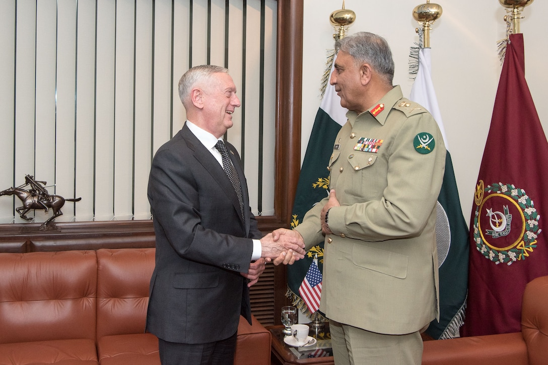 Defense Secretary James N. Mattis shakes hands with a Pakistani general in a room.
