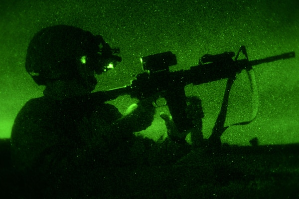 A service member wearing night vision goggles reloads an M4 carbine rifle during night-fire training at Joint Base San Antonio-Camp Bullis.