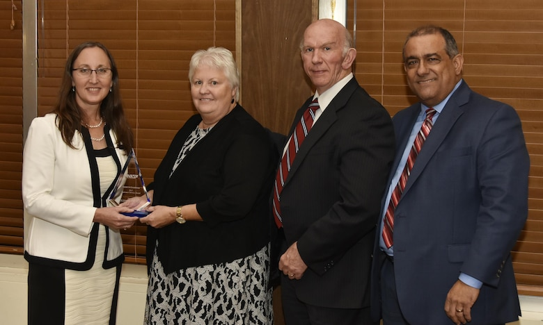 Judy Brewer (second from left), NAS administrative assistant, receives the Customer Service Award from NAS General Manager Cynthia Rivera during the National Aerospace Solutions 2017 Salute to Excellence Annual Awards Banquet held Nov. 16 at the Arnold Lakeside Center, Arnold Air Force Base, Tenn.. NAS Deputy General Manager Doug Pearson and NAS Business Services Manager Miguel Lugo are pictured at right. (U.S. Air Force photo/Rick Goodfriend)
