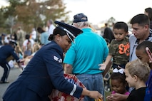 Senior Airman Jamie Smith, Moody Air Force Base ceremonial guardsman, passes out candy during a parade at the Tree Lighting Ceremony, Dec. 1, 2017, at Moody AFB, Ga. The annual event brings the base community together as a way to show thanks for their continuous sacrifice and celebrate the holiday season. The celebration included a parade, raffle give-a-ways, children's activities and traditional lighting of the base Christmas tree by families of deployed Airmen. (U.S. Air Force photo by Airman 1st Class Erick Requadt)