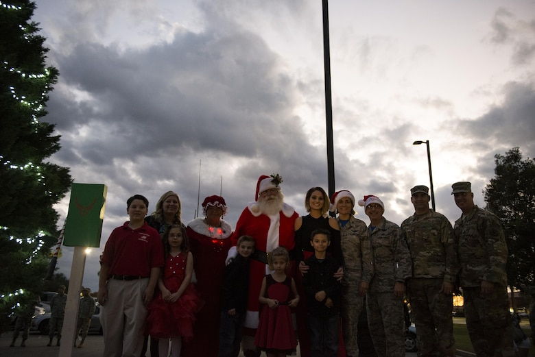 Members of Team Moody along with Santa and Mrs. Claus pose for a photo during the Tree Lighting Ceremony, Dec. 1, 2017, at Moody Air Force Base, Ga. The annual event brings the base community together as a way to show thanks for their continuous sacrifice and celebrate the holiday season. The celebration included a parade, raffle give-a-ways, children's activities and traditional lighting of the base Christmas tree by families of deployed Airmen. (U.S. Air Force photo by Airman 1st Class Erick Requadt)