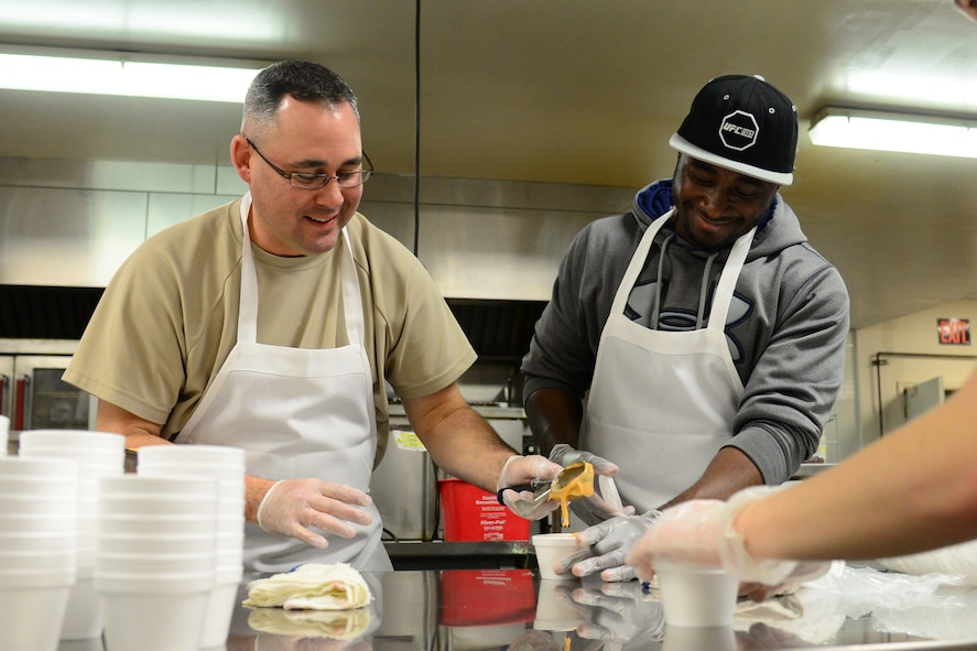 (Left) Master Sgt. Paul Watts, 341st Civil Engineer Squadron first sergeant, and Staff Sgt. Moses Adenolda, 341st Security Forces Squadron command support staff, cup butterscotch pudding for Meals on Wheels Nov. 22, 2017, in Great Falls, Mont. Desserts are provided with each meal prepared for the Thanksgiving holiday. (U.S. Air Force photo by Airman 1st Class Tristan Truesdell)