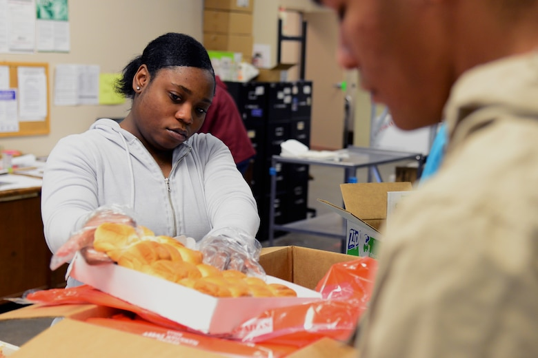 Airman 1st Class Destini Vance, 341st Force Support Squadron customer support apprentice, pulls rolls out of a box during Meals on Wheels meal preparation Nov. 22, 2017, in Great Falls, Mont. Food is divided into single-person servings for proper nutrition. (U.S. Air Force photo by Airman 1st Class Tristan Truesdell)