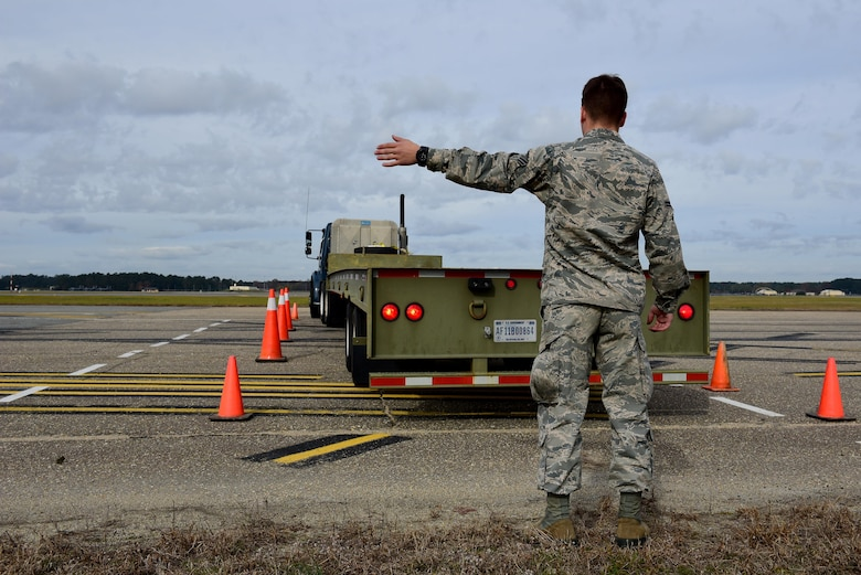 Airman 1st Class Cole Dredge, 4th Logistics Readiness Squadron vehicle operator, helps direct a tractor trailer into a parking spot during training, Nov. 21, 2017, at Seymour Johnson Air Force Base, North Carolina. During the 336th Fighter Squadron's deployment, October 2017, two Airmen drove a tractor trailer containing 16,000 pounds of equipment from Seymour Johnson AFB to Canadian Forces Base Greenwood, Nova Scotia, Canada to provide parts for diverted aircraft. (U.S. Air Force photo by Airman 1st Class Kenneth Boyton)
