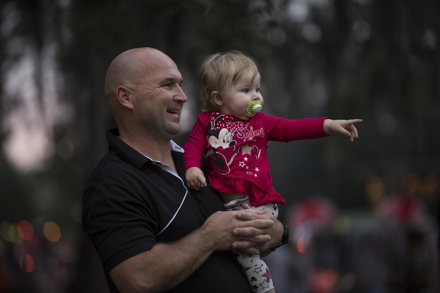 Senior Master Sgt. Matt Jenkins, 23d Maintenance Group weapons standardization section superintendent, watches the parade with daughter Etta, Dec. 1, 2017, at Moody Air Force Base, Ga. The annual event brings the base community together as a way to show thanks for their continuous sacrifice and celebrate the holiday season. The celebration included a parade, raffle give-a-ways, children's activities and traditional lighting of the base Christmas tree by families of deployed Airmen. (U.S. Air Force photo by Andrea Jenkins)