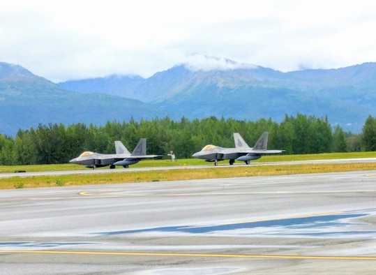Two F-22 Raptors prepare to take off during an Air Force Operational Energy mission at Joint Base Elmendorf-Richardson in Anchorage, Alaska, Aug. 13, 2017. The aircraft were part of a demonstration to assess if flying at an increased speed consumes less fuel while saving precious flight hours. (U.S. Air Force photo by Corrie Poland)