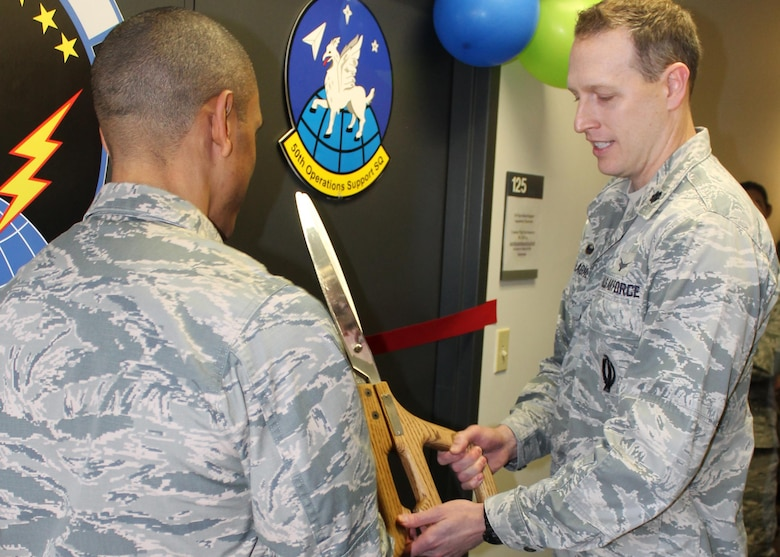 Lt. Col. David Gallagher, 50th Operations Support Squadron commander, and Lt. Col. Kelvin Dumas, 310th OSS commander, prepare to cut the ribbon marking the opening of their new training classroom dubbed 'The Hornet's Nest' on Friday, Dec. 1st, 2017.