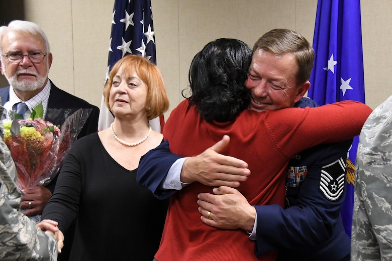U.S. Air Force Senior Master Sgt. Darren Ellingwood, 307th Operations Support Squadron intelligence superintendent, embraces a coworker at the conclusion of his retirement ceremony at Barksdale Air Force Base, La., Dec. 2, 2017.