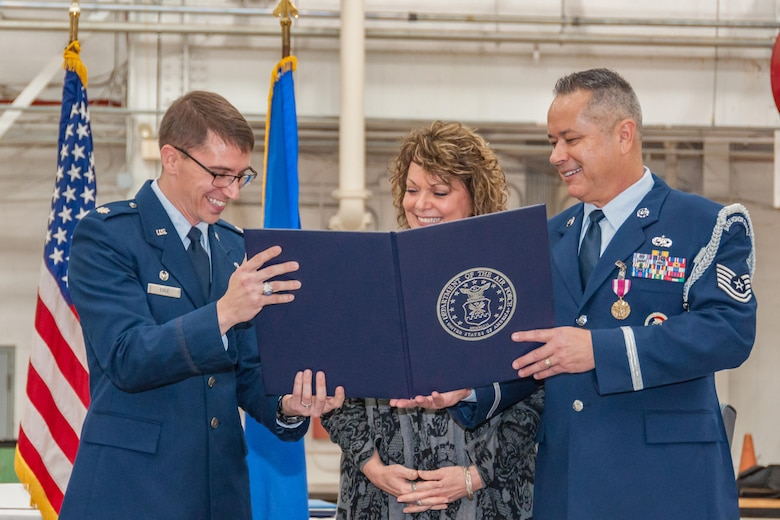 U.S. Air Force Lt. Col. George Cole, 307th Maintenance Squadron commander, and Tech. Sgt. Christopher Marien, 307th MXS Aerospace Ground Equipment mechanic, presents Marien's wife, Sheri, with a certificate of appreciation during Marien's retirement ceremony on Barksdale Air Force Base, La., Dec. 2, 2017.