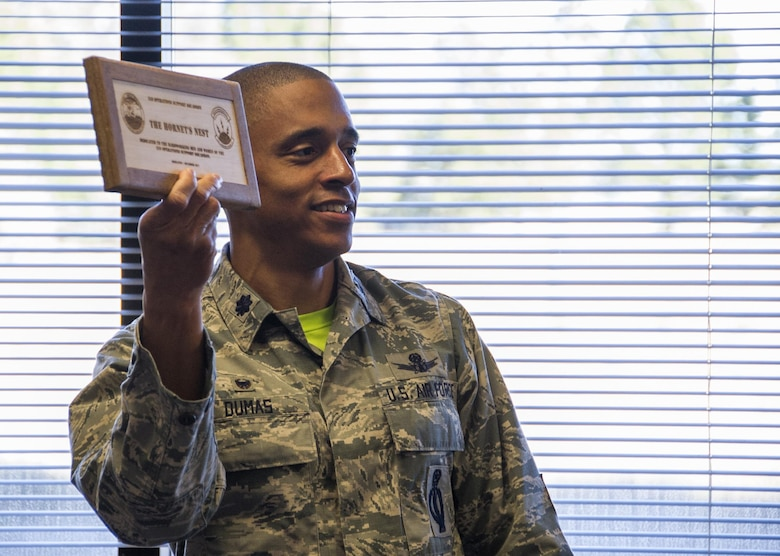 Lt. Col. Kelvin Dumas, 310th Space Operations Squadron commander, holds up the official plaque assigning a name to the new 310th OSS classroom on Friday, Dec. 1st, 2017.