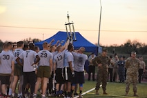 U.S Navy and Marines join around the trophy after winning the Army-Navy game at the Mathis Fitness Center field Dec. 1. This is the Navy's second win in 14 years. (U.S. Air Force photo by Airman 1st Class Zachary Chapman/Released)