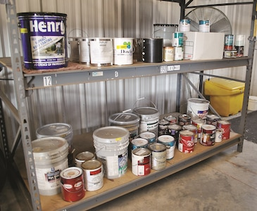 Paint products sit on a shelf at the Hazardous Materials Processing Center to be reissued to a unit or on-post organization for reuse after being previously turned in to the HMPC.
