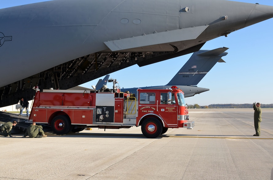 Loadmasters from the 89th Airlift Squadron load a fire truck on a 445th Airlift Wing C-17 Globemaster III Nov. 8, 2017. The wing received a request through the Denton Program to move a fire truck from Ohio to Belize City, Belize.