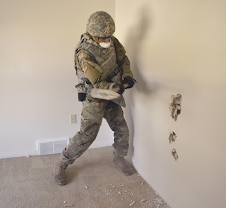 First Lt. Nicholas Framo, 774th Ordnance Company, 242nd Ordnance Battalion, 71st Ordnance Group (Explosive Ordnance Disposal), attacks a wall with a sledgehammer during training at the Colyer Manor housing area Nov. 16. The houses in the area have been targeted for demolition, providing an opportunity to train for EOD personnel.