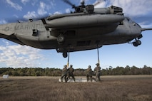 Marines with Combat Logistics Battalion 6, 2nd Marine Logistics Group attach cables and practice materials to a CH-53E Super Stallion during Helicopter Support Team training at Camp Lejeune, N.C., Nov. 28, 2017. A Helicopter Support Team is comprised of approximately eight landing support specialist Marines who ensure the equipment is properly attached and secured before pilots transport the gear or supplies to their destination. (U.S. Marine Corps photo by Cpl. Aaron Henson)