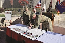 """Maj. Gen. Joseph M. Martin, 1st Infantry Division and Fort Riley commanding general, signs the """"Commitment to Our Military Families,"""" and the """"Healthcare Resource Sharing Agreement with Veteran Affairs Eastern Kansas Health Care System"""" proclamations during the Patient and Family Covenant Signing at the Irwin Army Community Hospital community garden Nov. 15."""