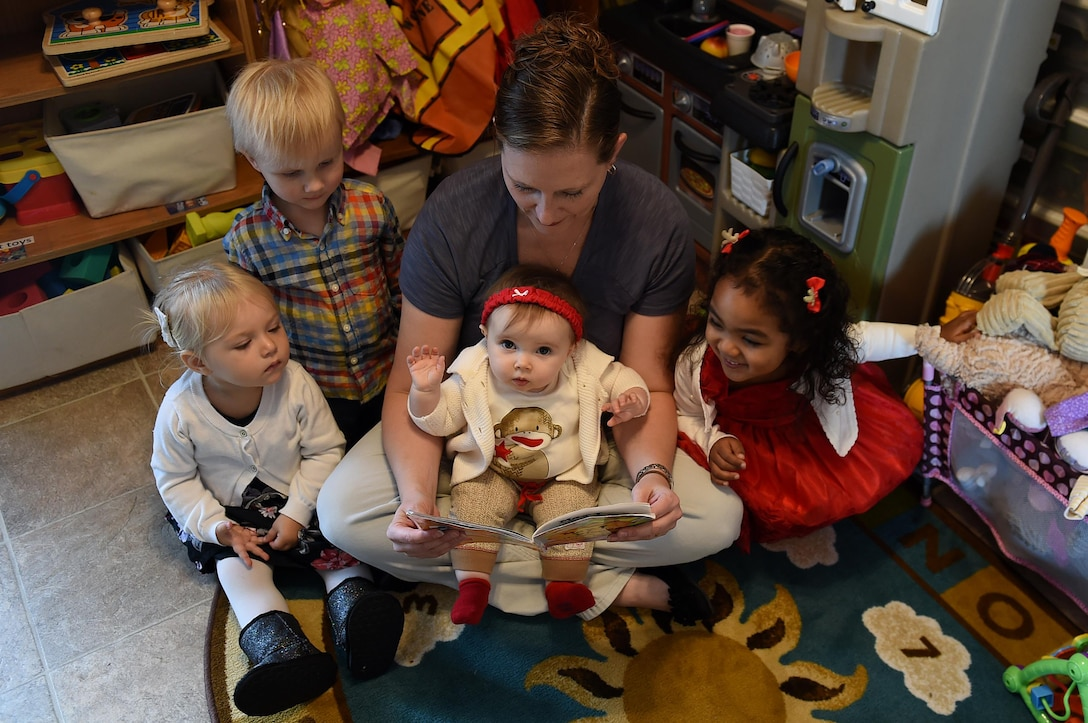 Woman reads book to group of children