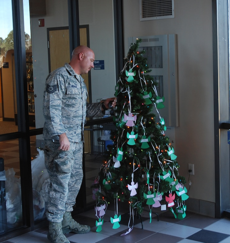 PETERSON AIR FORCE BASE, Colo. – Tech. Sgt. David Rediger, 302nd Airlift Wing Civil Engineer Squadron Explosive Ordinance Disposal, technician, takes a moment to view the angels on the Angel Tree in the entryway of the 21st Mission Support Group headquarters in building 350 at Peterson Air Force Base, Colorado Dec. 1, 2017.