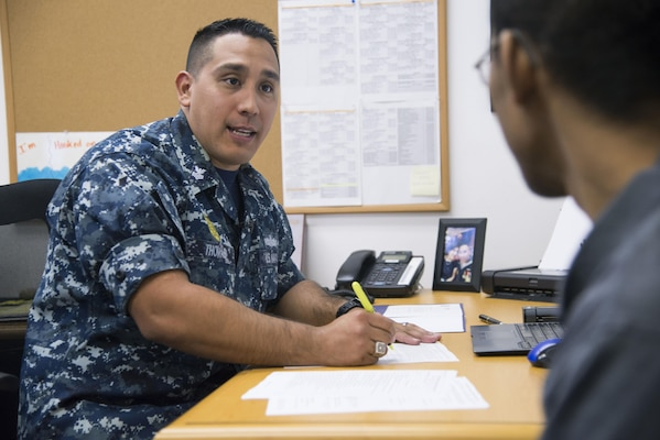 Petty Officer First Class Christopher Thomas, Navy Recruiting District San Antonio recruiter, speaks to an applicant about job opportunities in the Navy Oct. 25, 2017.  Thomas' mission is to find officer applicants to lead naval forces in conducting operations on land, air and sea.  (U.S. Air Force photo by Sean M. Worrell)