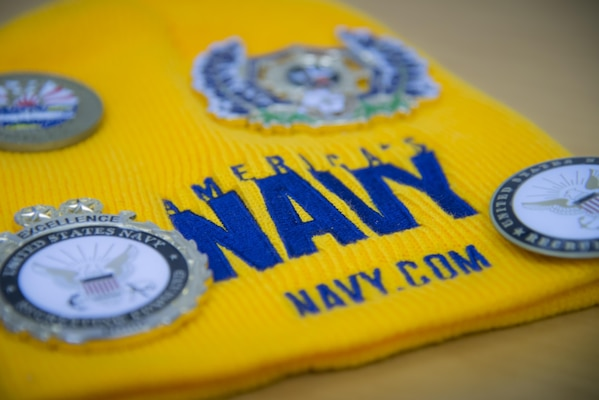 An America's Navy hat laying on Petty Officer First Class Christopher Thomas, Navy Recruiting District San Antonio recruiter, desk Oct. 25, 2017.  Thomas' mission is to find officer applicants to lead naval forces in conducting operations on land, air and sea.  (U.S. Air Force photo by Sean M. Worrell)