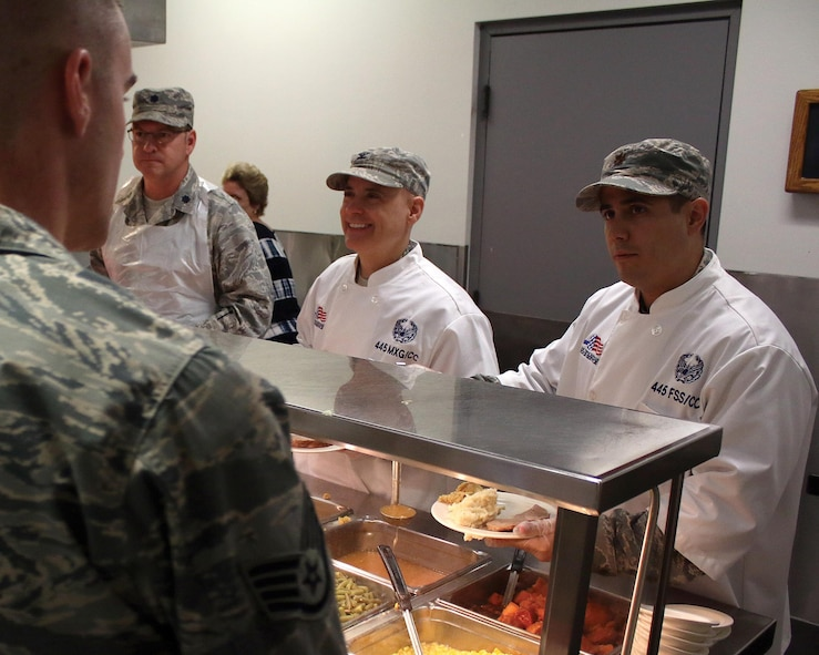 Lt. Col. Todd Reeder, 445th Maintenance Squadron commander; Col.  Cade Gibson, 445th Maintenance Group commander; and Maj. Jason Miller, 445th Force Support Squadron commander, serve holiday meals to Airmen at the Pitsenbarger Dining Facility Nov. 5, 2017.