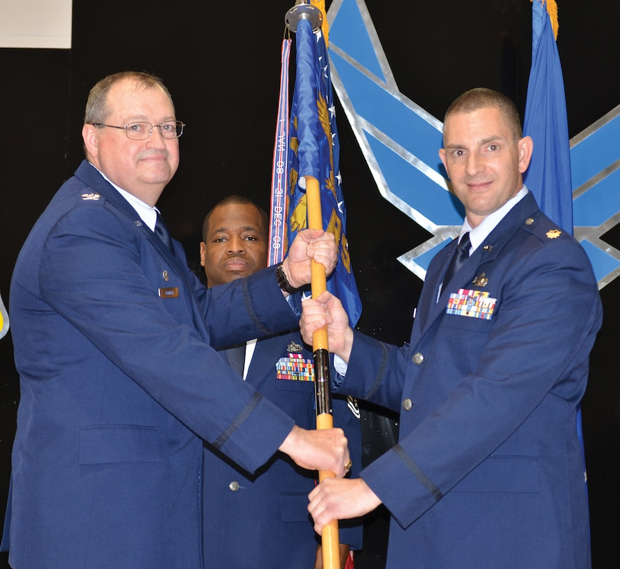 Col. Bryan Runion, 445th Mission Support Group commander, passes the guidon to Maj. Jason Vance, incoming 445th Logistics Readiness Squadron commander at the LRS change of command ceremony, Nov. 5, 2017.